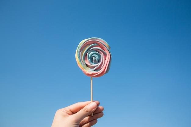 Caramelo de la piruleta en fondo del cielo azul. concepto de verano de comida de hipster.