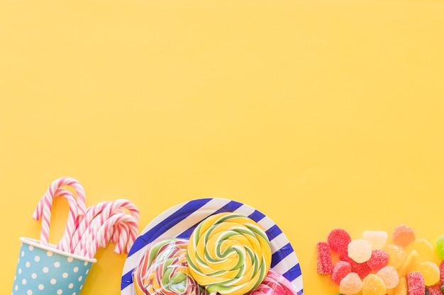 Caramelos de azúcar de menta, piruletas y caramelos de gelatina de azúcar sobre fondo amarillo