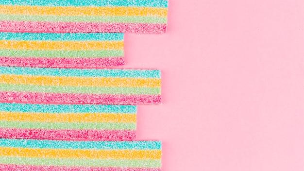Caramelos de azúcar rayados coloridos en fondo rosado