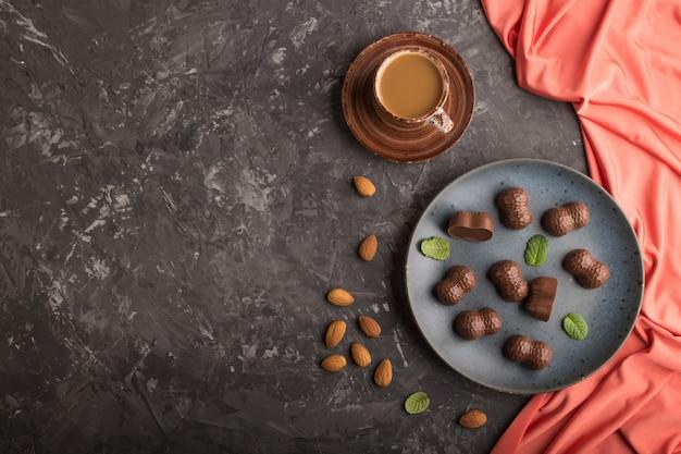 Caramelos de chocolate con almendras y una taza de café sobre un fondo de hormigón negro. vista superior, espacio de copia.