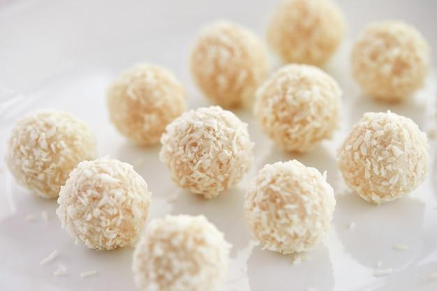 Caramelos de chocolate blanco con relleno de coco sobre un fondo blanco.