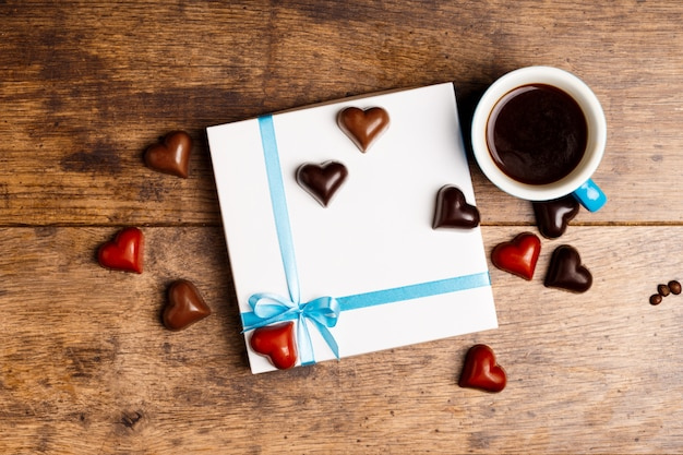 Caramelos de chocolate y café sobre madera.