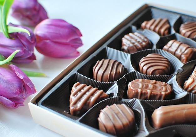 Caramelos de chocolate en caja y tulipanes morados, regalo del día de san valentín.