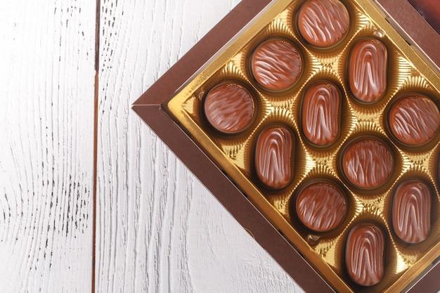 Caramelos de chocolate en caja, vista cercana en mesa blanca