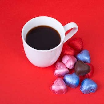 Caramelos de chocolate en forma de corazón con taza de café