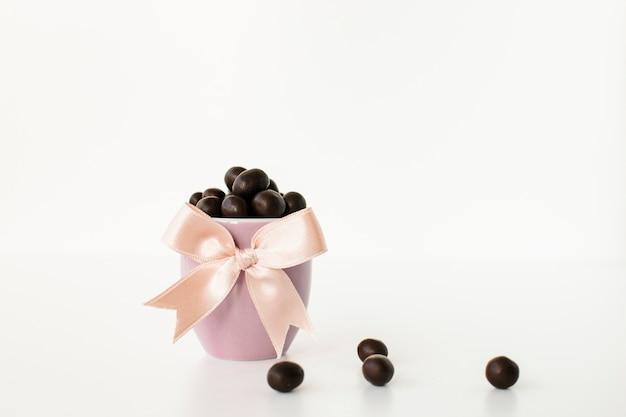 Caramelos de chocolate en un tazón rosa con cinta