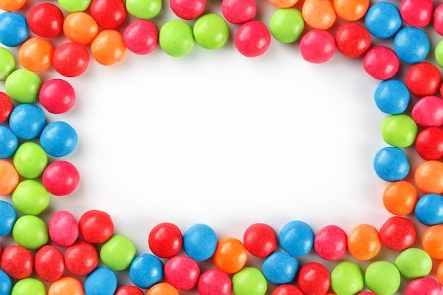 Caramelos de color arco iris sobre fondo blanco.