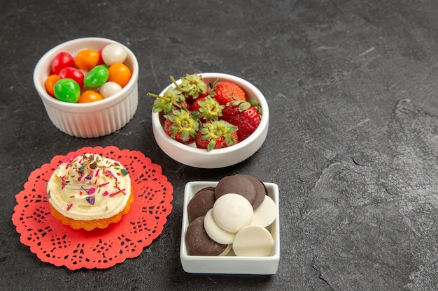 Caramelos de colores con galletas y fresas en la oscuridad