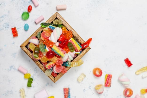Caramelos de colores, gelatina, malvavisco en la superficie de la luz. vista superior con espacio de copia
