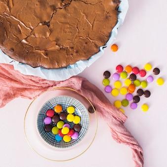 Caramelos de colores junto a pastel de chocolate endecha plana.