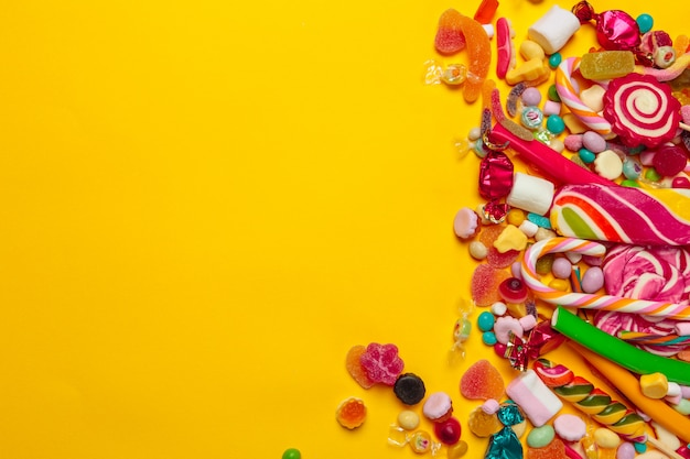 Caramelos de colores sobre fondo amarillo con copyspace