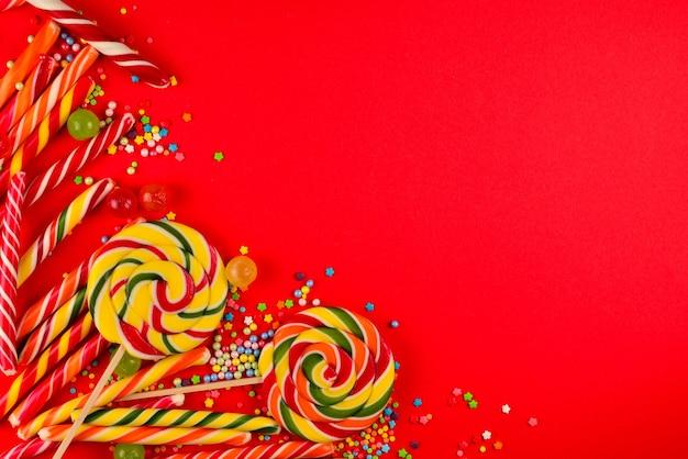 Caramelos de colores sobre un fondo rojo.