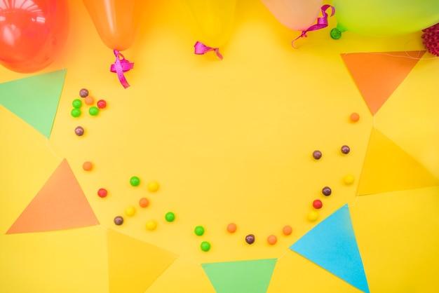 Caramelos coloridos con empavesado y globos sobre fondo amarillo