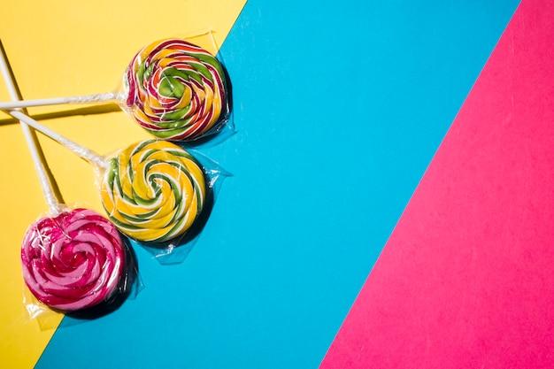 Caramelos coloridos piruletas en fondo colorido rayado