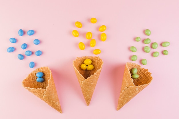 Caramelos coloridos que se derraman del cono de la galleta del helado en fondo rosado