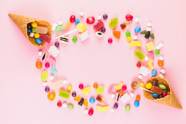 Caramelos dulces coloridos con dos helados cono de galleta en superficie rosa