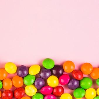 Caramelos dulces coloridos en fondo rosado
