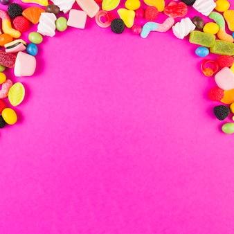 Caramelos dulces coloridos que forman forma del arco en el contexto rosado