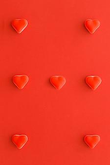 Caramelos dulces en forma de corazón sobre fondo rojo