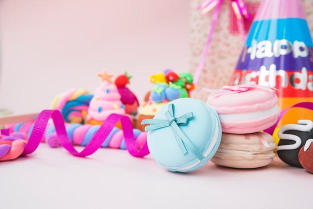 Caramelos dulces; macarrón; cintas y sombrero de cumpleaños en fondo rosa
