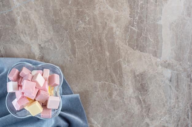 Caramelos dulces rosados en un tazón de vidrio sobre fondo gris.
