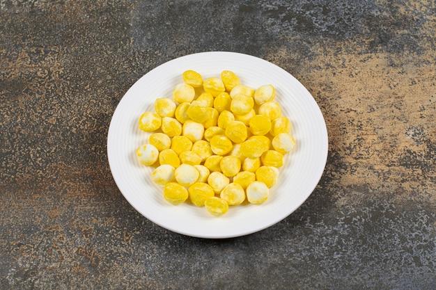 Caramelos duros amarillos en un plato blanco.