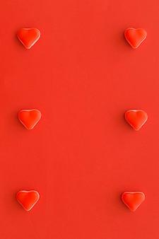 Caramelos en forma de corazón en una fila en el contexto rojo