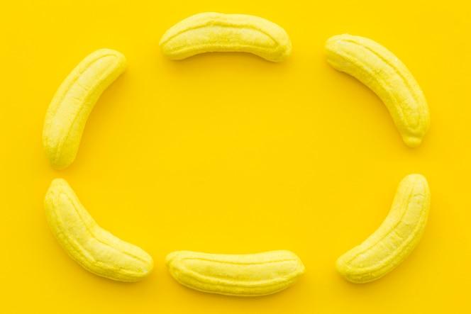 Caramelos en forma de plátano formando marco sobre fondo amarillo
