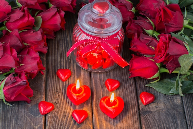 Caramelos en forma de corazón en un frasco de vidrio, rosas rojas y velas