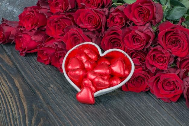 Caramelos en forma de corazón y un ramo de rosas rojas