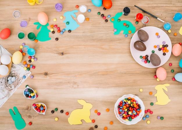 Caramelos de gemas de colores; huevos de pascua; colores y pincel en escritorio de madera