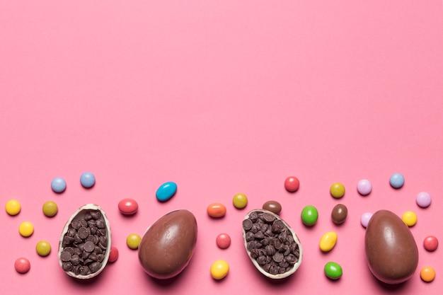 Caramelos de gemas; huevos de pascua de chocolate rellenos de chips de choco sobre fondo rosa