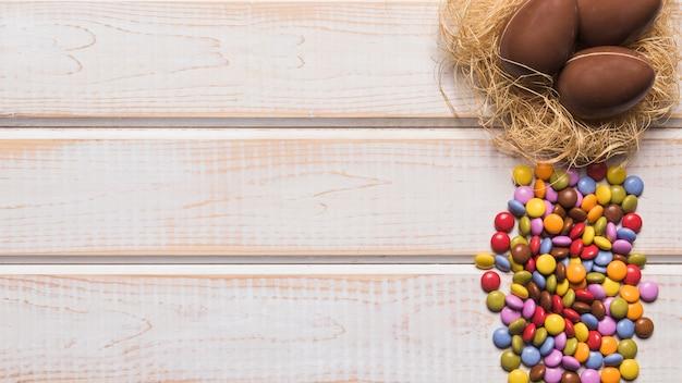 Caramelos de gemas multicolores cerca de los huevos de chocolate en el nido sobre el escritorio de madera