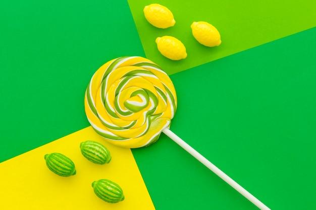 Caramelos y lollipop en contrato de fondo de papel de color