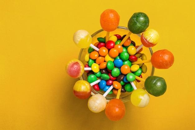 Caramelos multicolores y piruletas en el cristal sobre fondo amarillo