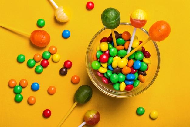 Caramelos multicolores y piruletas sobre fondo amarillo