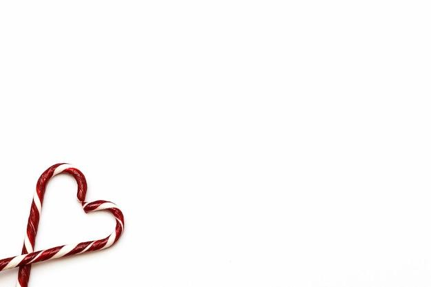Caramelos de navidad doblados en forma de corazón sobre un fondo blanco.