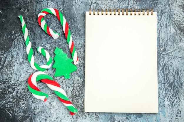 Caramelos de navidad de vista superior un bloc de notas en superficie gris