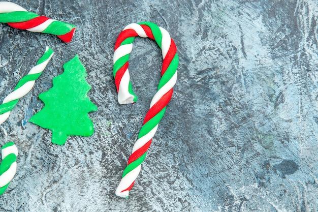 Caramelos de navidad de vista superior en superficie gris