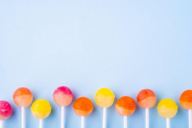 Caramelos de piruleta en fila en la vista superior azul
