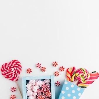 Caramelos y piruletas en mesa blanca con espacio de copia