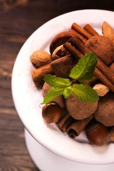 Caramelos de trufas de chocolate y surtido de nueces en soporte blanco