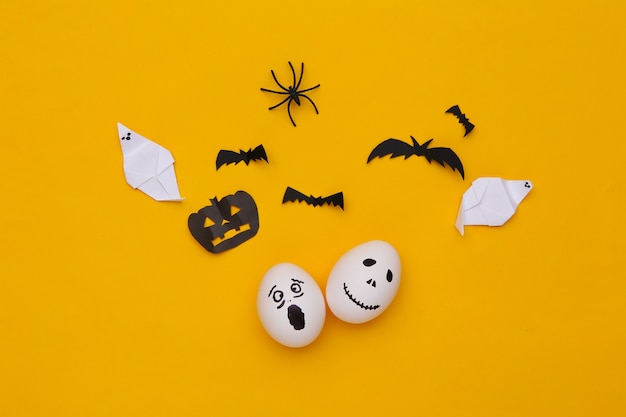 Caras de huevo con decoración de halloween sobre fondo amarillo. vista superior