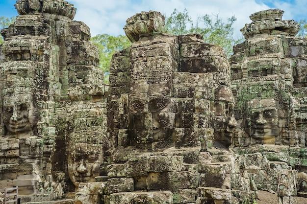 Caras de piedra antiguas en el cielo azul nublado del templo de bayon, angkor wat, siam reap, camboya.