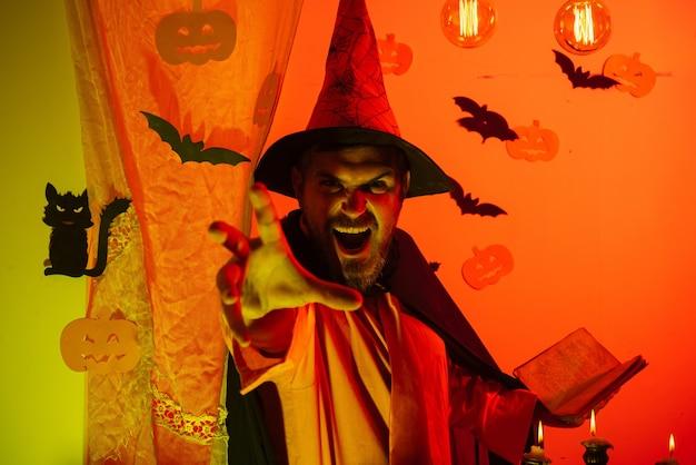 Caras de terror de hombre. hombre asustadizo leyendo un libro mágico con hechizos. padre sobre fondo de halloween con libro de magik. fiesta de halloween con divertidos disfraces de carnaval para padre.
