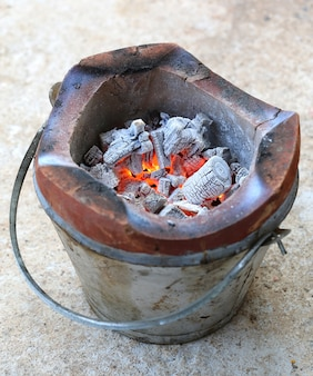 Carbón de leña al fuego sobre la estufa vintage.