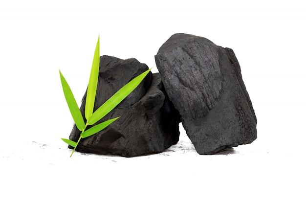 Carbón de leña natural, polvo de carbón de bambú tiene propiedades medicinales con carbón tradicional aislado sobre fondo blanco.