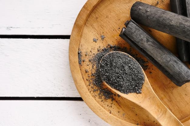 Carbón de leña y polvo de bambú en la tabla de madera. copia espacio
