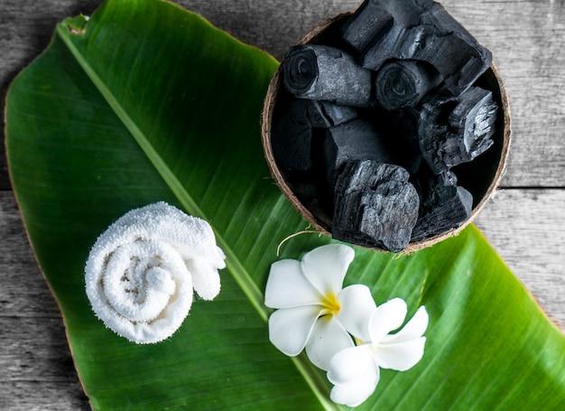 Carbón vegetal en cáscara de coco para spa en el fondo de madera con toalla blanca y flor en hoja de plátano