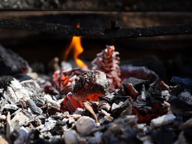 Carbones humeantes anaranjados y llamas bajas en barbacoa